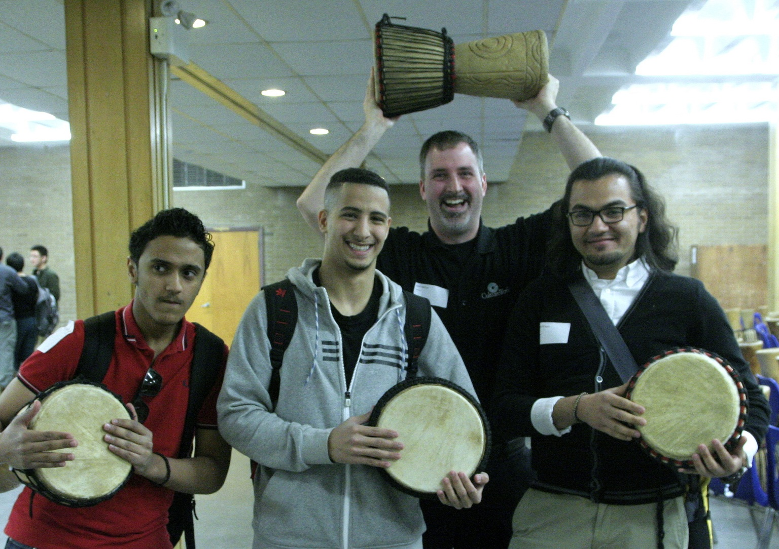 A teacher has fun with CultureWorks students at the Drum Café Activity