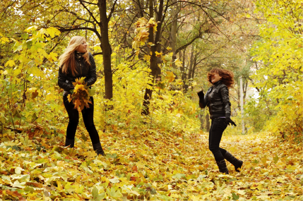 Two students play around in beautiful autumn leaves