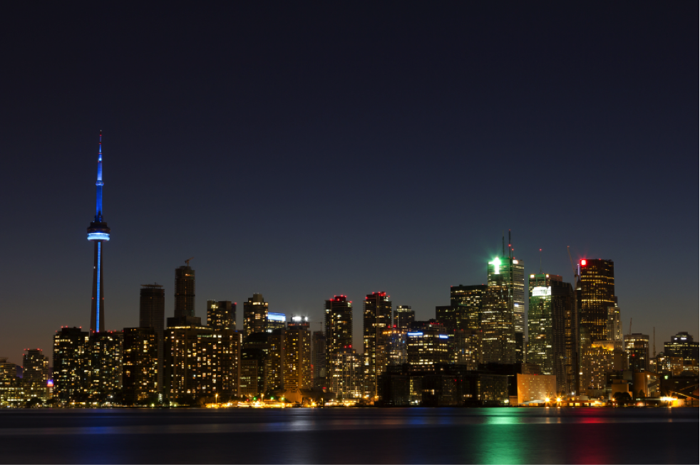 The CN Tower lit up at night against the Toronto skyline